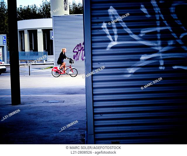 Young woman riding on a Bicing bicycle. Barcelona, Catalonia, Spain