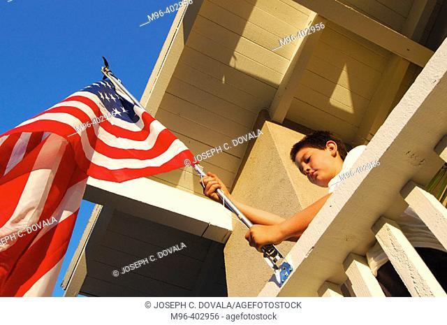 Boy raising American flag on his house
