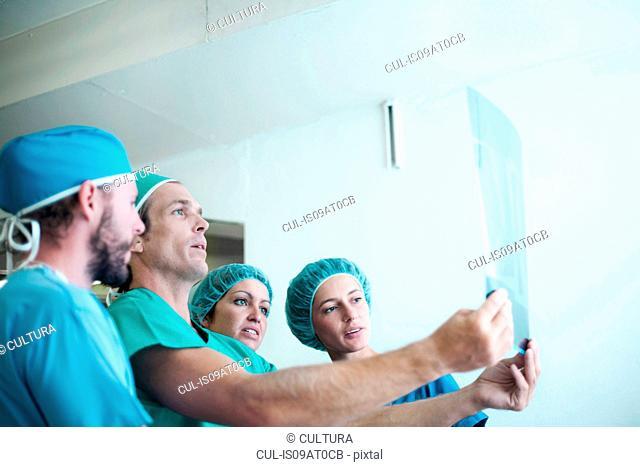 Four male and female orthopedic surgeons examining x-ray image