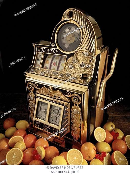 Antique slot machine near cut fruit