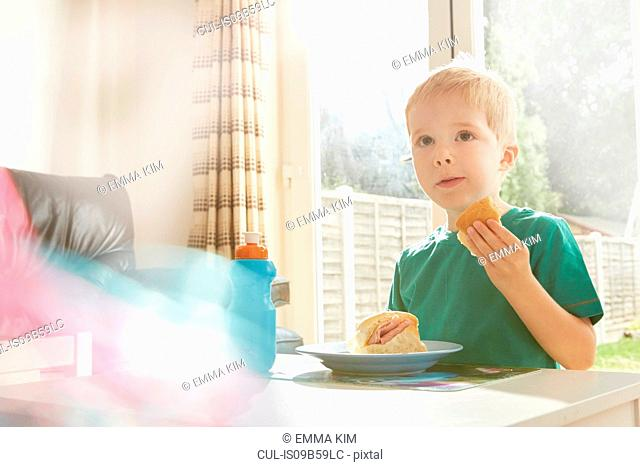 Boy eating sandwich at table