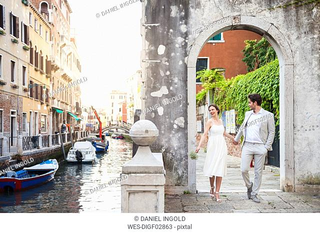 Italy, Venice, bridal couple walking hand in hand through archway