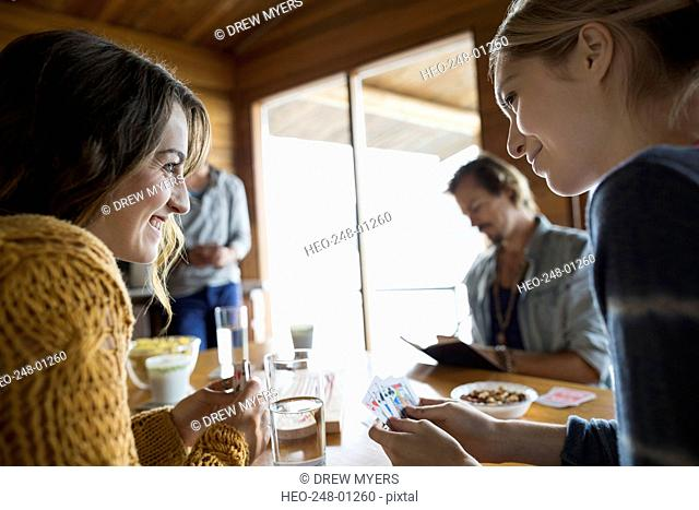 Young friends playing cribbage at table