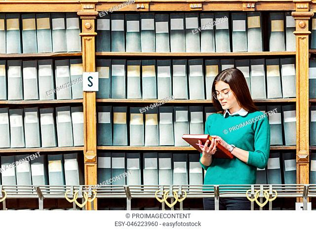 Slender brunette wearing stylish glasses and green sweater holds red book near library bookshelves with grey boxes