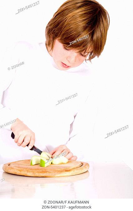 Young boy cuts the apple