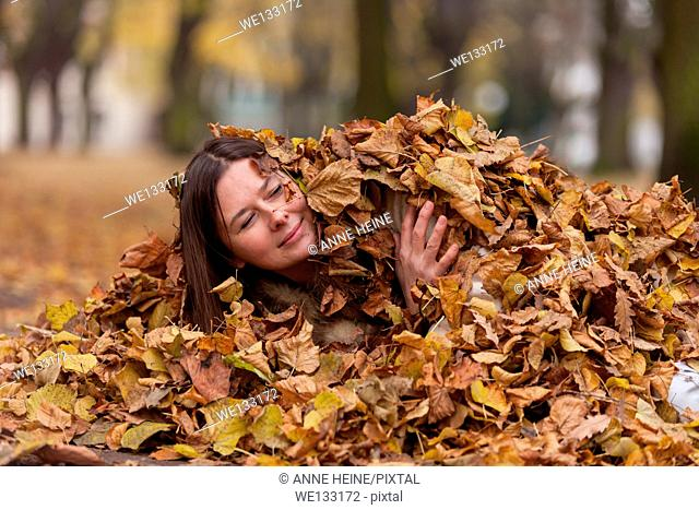 Woman peeking with head out of heap of leaves
