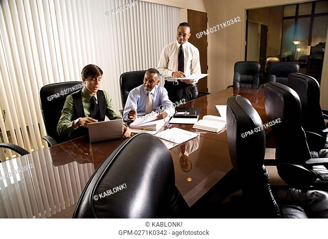 Employees assisting African American executive reviewing paperwork in conference room