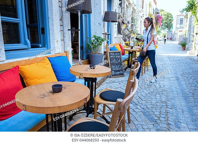 Unidentified People walk at a street with cafe and restaurant with tables and chairs around at Alacati Town,a popular destination for traveling and vacation in...