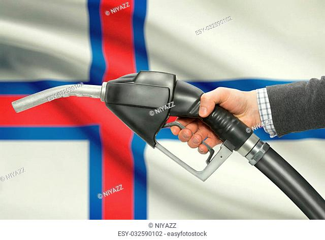 Fuel pump nozzle in hand with flag on background - Faroe Islands