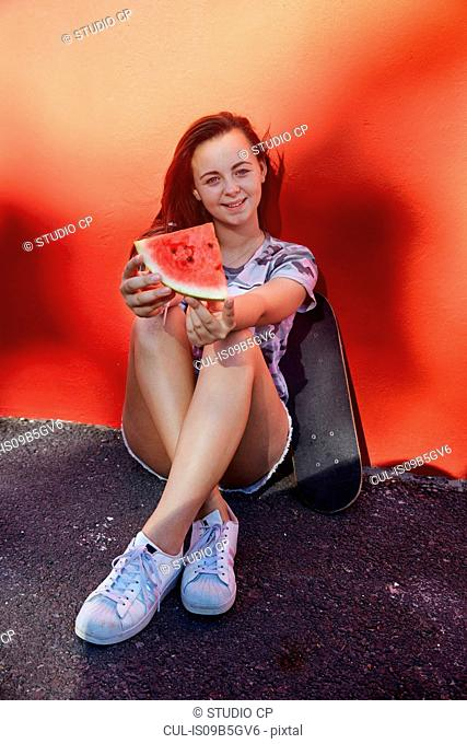 Teenage girl with watermelon and skateboard, red wall in background