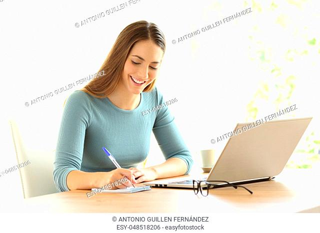Happy woman writing notes beside a laptop on a desk at home