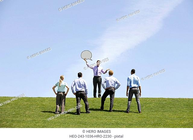 Businessman displaying speech bubble to colleagues outdoors