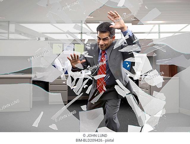 Businessman crashing through office window