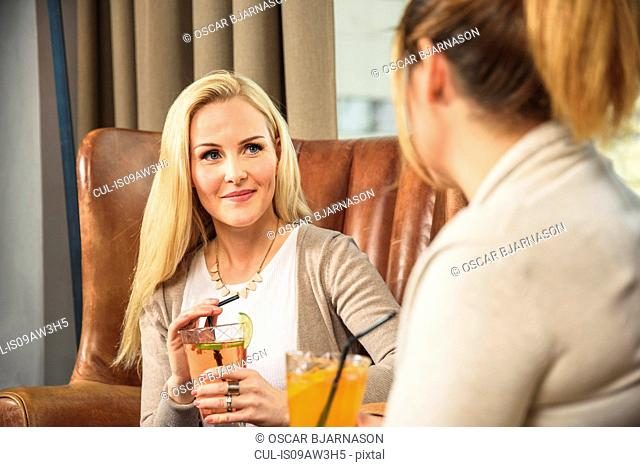 Mid adult women in bar sitting in leather armchair holding cocktail smiling at friend