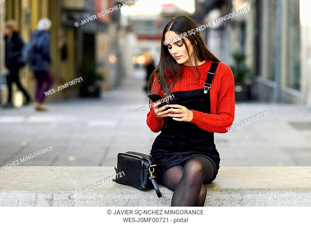 Portrait of fashionable young woman sitting on bench at pedestrian area looking at cell phone