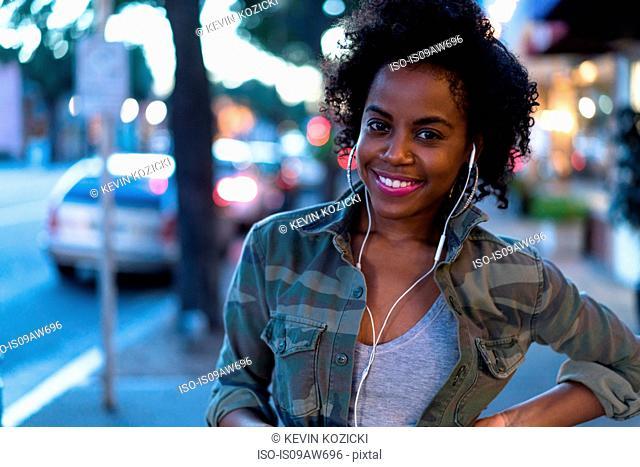 Woman standing in street, wearing earphones, smiling
