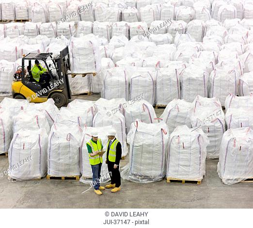 Businessman and workers among large bags of recycled plastic pellets in warehouse