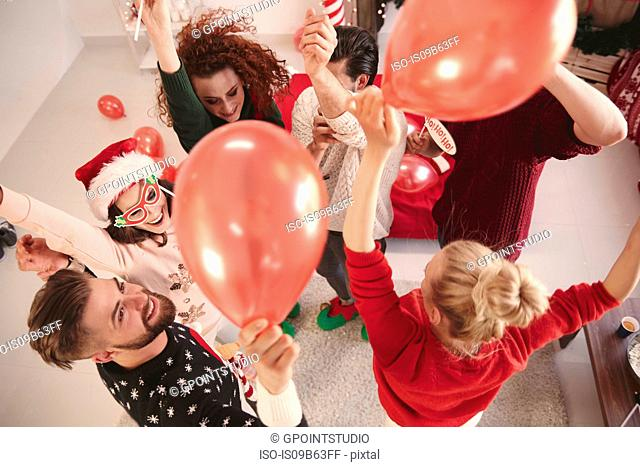 Overhead view of young adult friends dancing with balloons at christmas party
