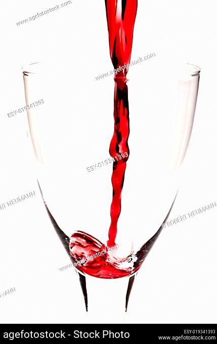 Rotwein fließt ins Weinglas V1