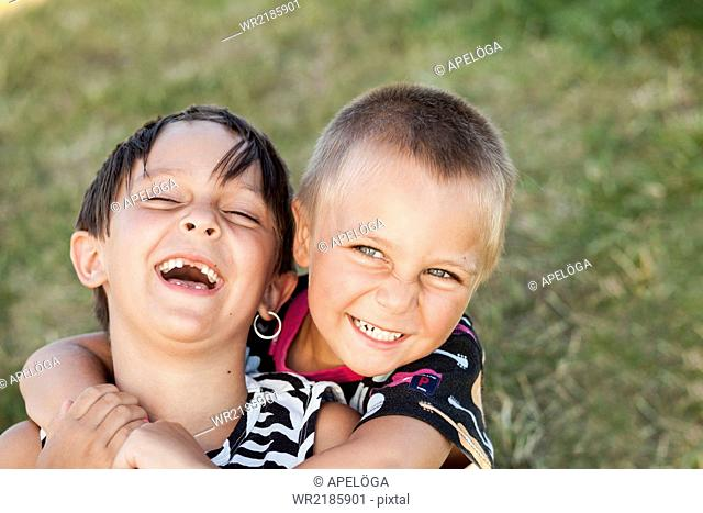 Happy brother embracing sister in park