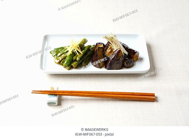 Eggplant in plate with chopsticks, close-up