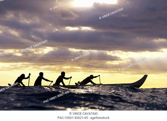 Outrigger canoe and paddlers silhouetted at sunset, sunrays through the clouds