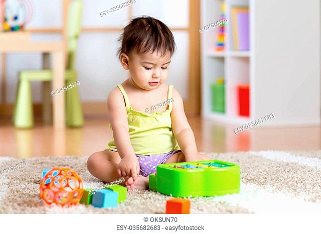 Child toddler with develepmental toys. Early education for kids. Colorful wooden art toys. Little girl play music. Kid with piano