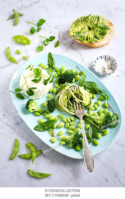 A green salad made of courgette spaghetti, Edamame beans, broccoli, water cress, bloodwort, baby spinach with ricotta, avocado bagel