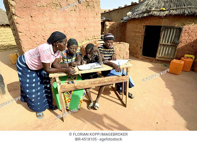 Teenage girls, 14 and 17 years, and boy, 9 years, doing homework with mother, village Koungo, Plateau Central, Burkina Faso