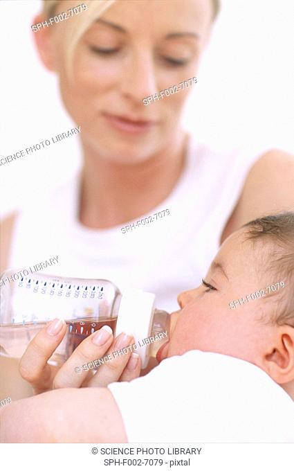 Mother bottle-feeding baby boy