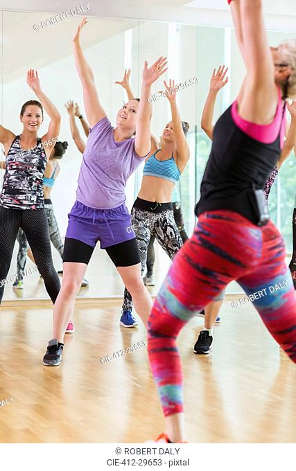 Women with arms raised in exercise class