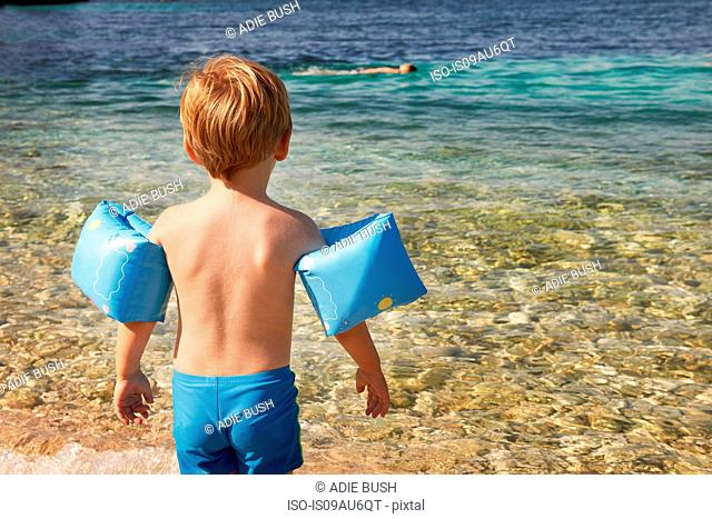 Rear view of cute boy wearing blue armbands paddling in sea