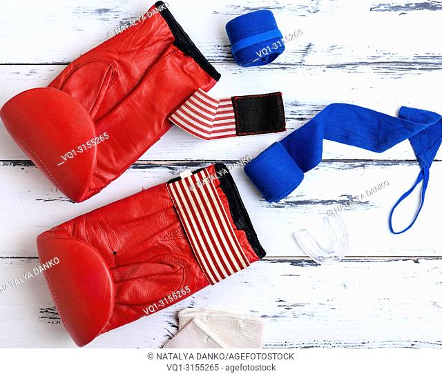 pair of red leather boxing gloves, blue textile bandage, silicone protection for teeth on a white wooden background, top view