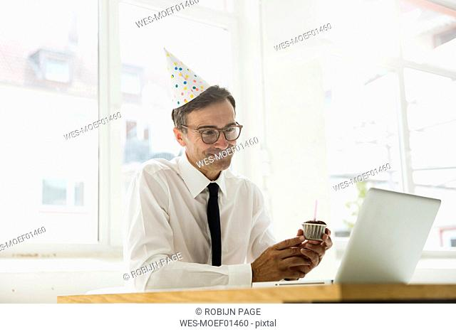 Businessman with laptop celebrating birthday in office