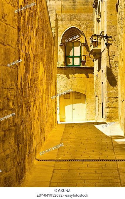 Narrow street with traditional maltese buildings in historical part of Mdina. The city was founded as Maleth in around the 8th century BC by Phoenician settlers...
