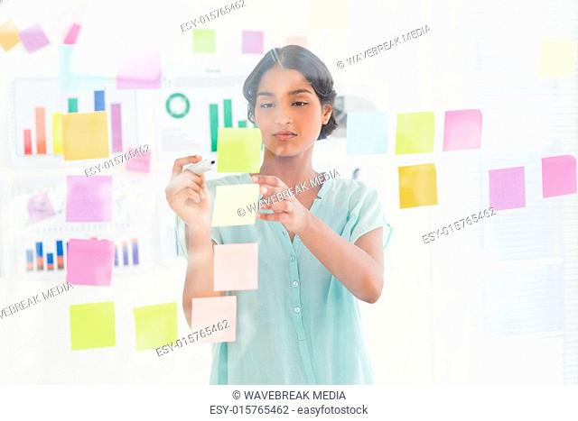 Concentrated businesswoman looking post its on the wall