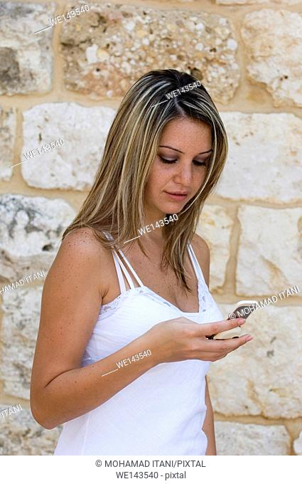 Blonde woman text messaging on mobile phone