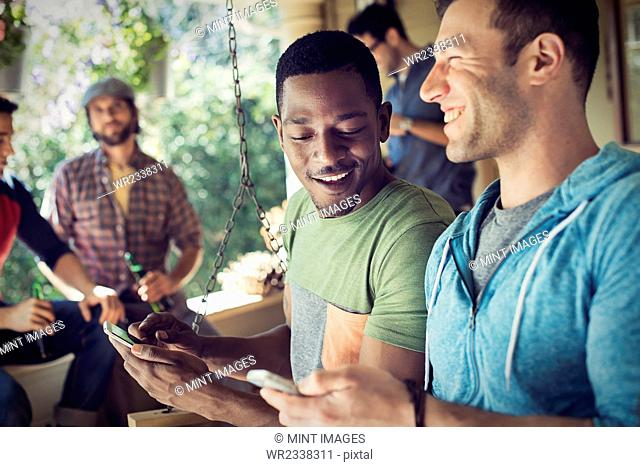 A group of friends, men and women at a house party, two men looking at their smart phones