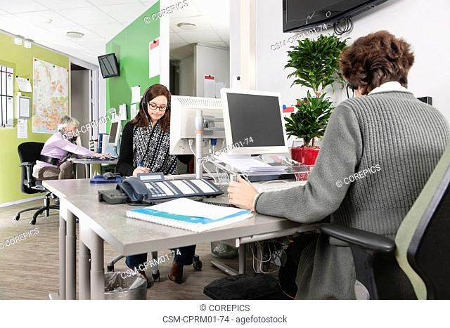 Returners working at the emergency call center of a hospital, answering phone calls from patients, making appointments