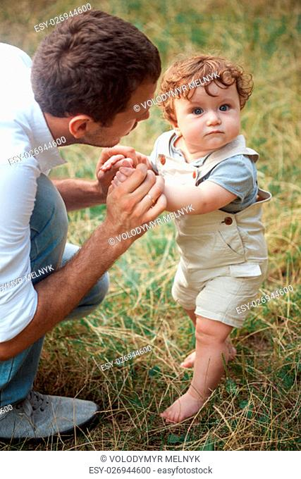 Young beautiful father and little toddler son against green grass. Happy father with her baby boy on a summer sunny day. Family walking on the meadow