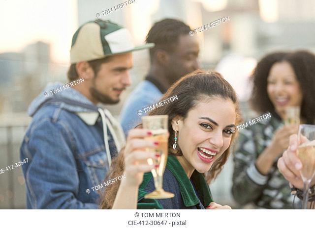 Portrait enthusiastic young woman drinking champagne at party