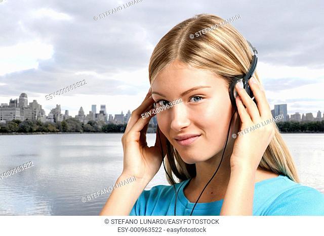 Teenage girl listening to the music, Manhattan skyline in the background