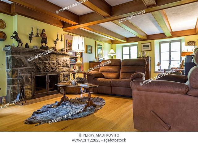 Brown upholstered sofas in living room with stone fireplace, wooden coffee table on top of a seal skin inside an old 1839 Canadiana fieldstone style house