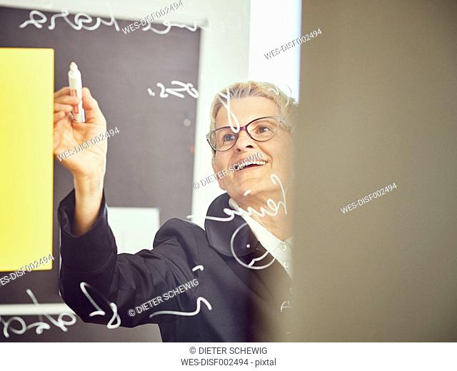 Woman writinging on glass pane in a classroom