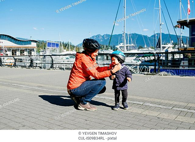 Mother putting protective helmet on son, British Columbia, Canada