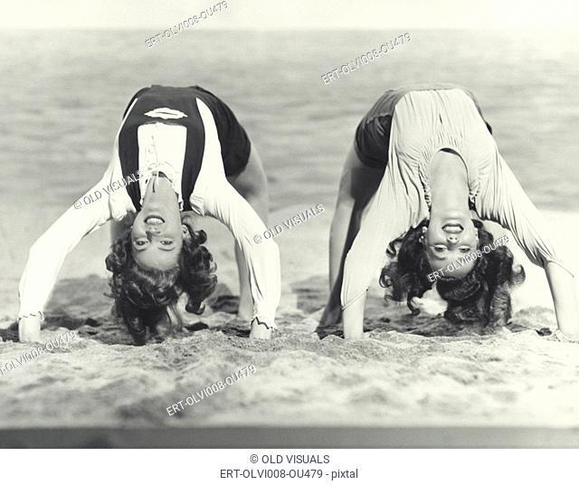 Two women doing backbends on the beach (OLVI008-OU479-F)