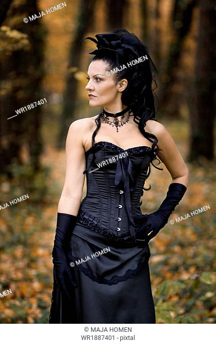 Young woman in Gothic style fashion stands in forest, Croatia, Europe