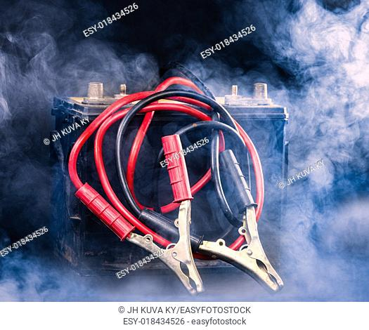Old car battery and the jumper cables, smoky environment