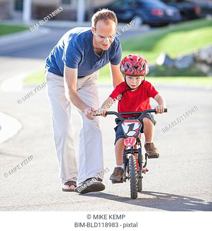 Caucasian father teaching son to ride bicycle