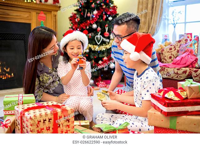 Chinese family opening their presents together on Christmas morning. they are all sitting on the floor in their living room, in front of the tree